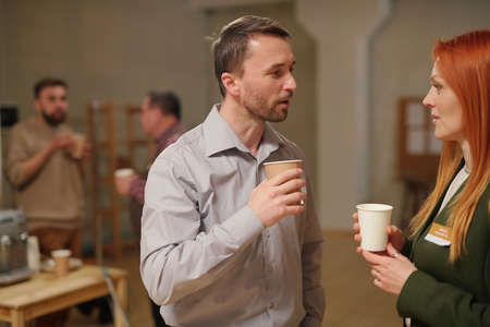 Middle aged man and woman with drinks interacting after session Фото со стока