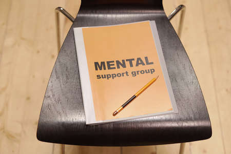 Mental support group journal on black wooden chair