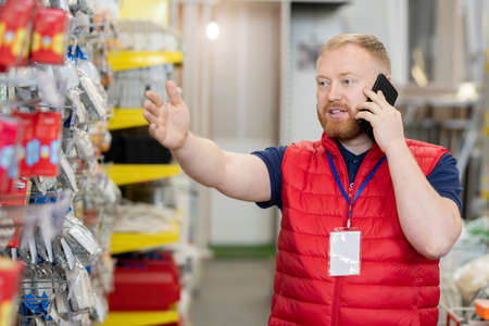 Shop assistant with smartphone showing at display with goods Фото со стока