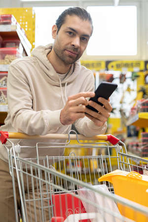 Young man scrolling in mobile phone over shopping cart in hardware store