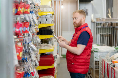 Male shop assistant in red uniform using tablet while checking goods in hardware supermarket