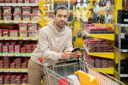 Young man with smartphone and shopping cart in hardware store Фото со стока
