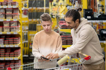Man and teenage boy looking through online goods in smartphone over shopping cart Фото со стока