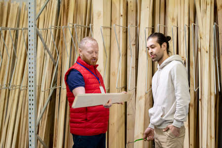 Shop assistant of hardware store helping young man to choose wooden board