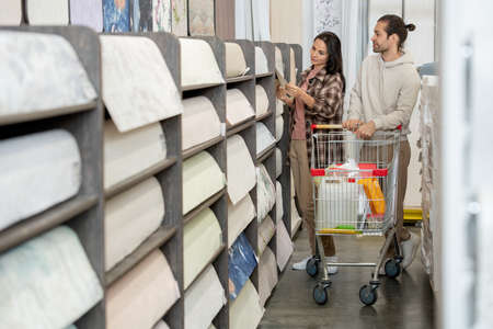 Young couple choosing household goods in large hardware store