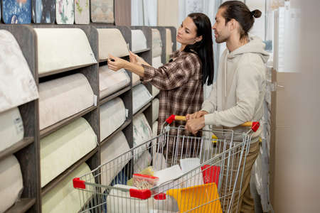 Young man and woman choosing new linoleum for their house or flat in hardware supermarket