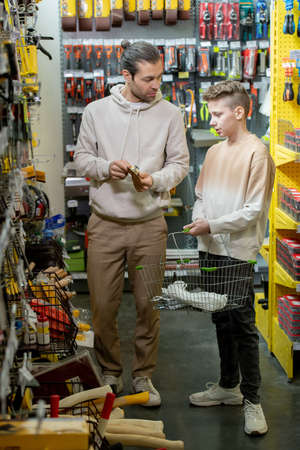 Father and son standing in one of departments of modern hardware store