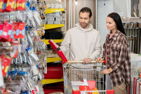 Husband and wife choosing household goods in hardware store