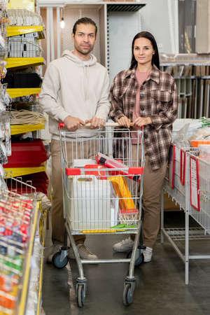 Young couple with shopping cart standing in hardware supermarket Фото со стока