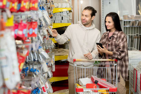 Young man and his wife buying household goods in contemporary hardware supermarket Фото со стока