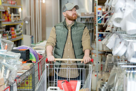 Young bearded man with shopping cart visiting hardware store