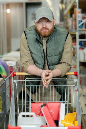 Bearded man leaning over shopping cart in hardware supermarket Фото со стока