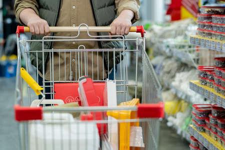 Man in casualwear pushing shopping cart while visiting supermarket