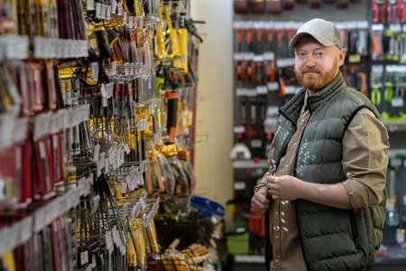 Bearded male customer with handtool standing by display with household goods