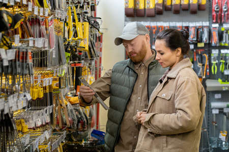 Middle aged couple choosing handtools in large hardware supermarket
