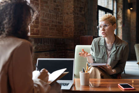 Two young businesswomen consulting at meeting while one of them making notes