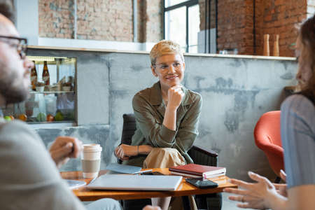 Successful businesswoman listening to one of colleagues at working meeting