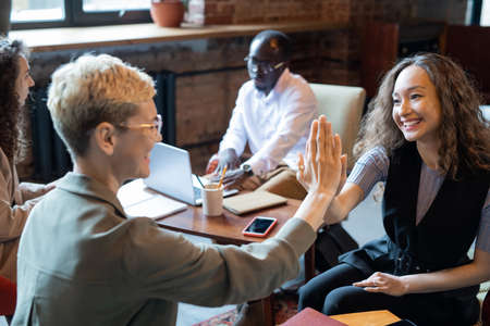 Happy young manager giving high five to elegant colleague at meeting