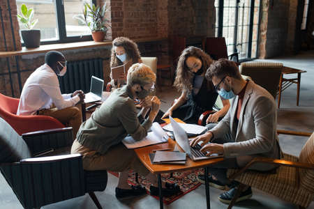 Business people in protective masks working by tables in office Фото со стока