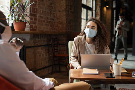 Female in mask listening to African colleague at start-up meeting