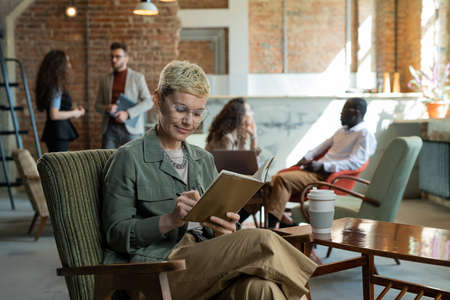 Young businesswoman making notes in notebook in working environment