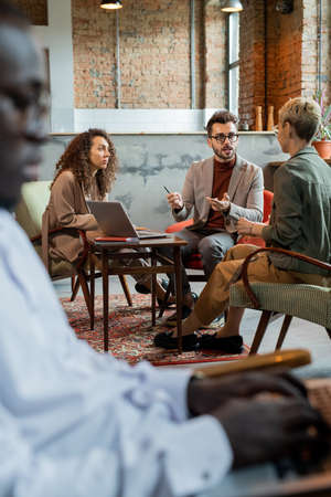 Confident business people interacting by table with African colleague in front