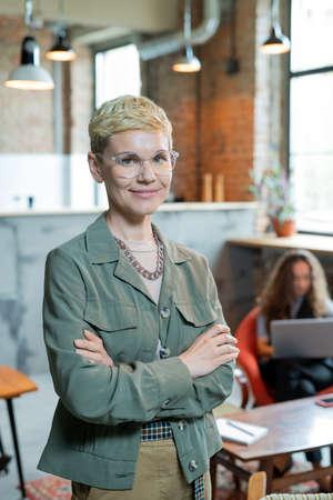 Blond successful businesswoman in elegant casualwear standing in office