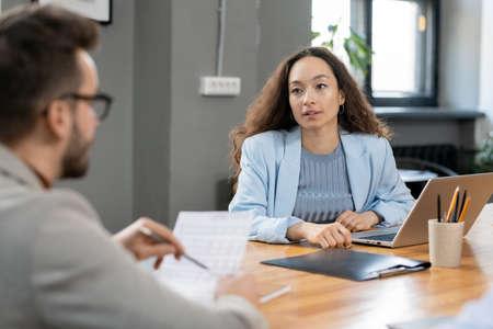Elegant pretty financier talking to colleague with paper