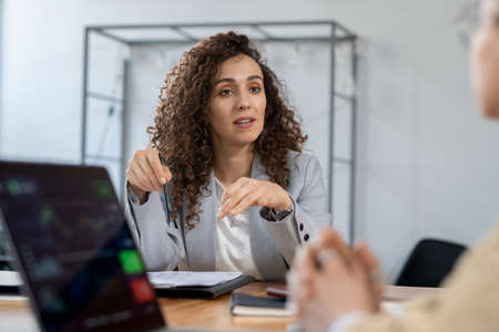 Confident businesswoman explaining one of contract points to partner Фото со стока