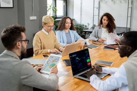 Large group of financier working individually by table in office Фото со стока