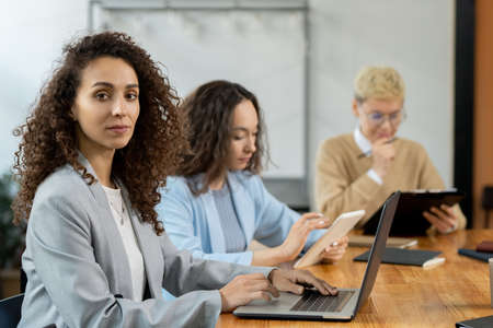 Attractive businesswoman with laptop sitting by table among co-workers