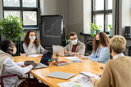 Group of colleagues in protective masks discussing working points at meeting in office