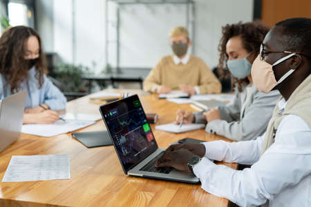 Young African businessman in protective mask and his colleagues working individually
