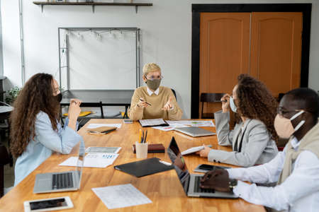 Two businesswomen in masks discussing new business perspectives in working environment