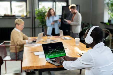 African businessman in headphones working with online data against colleagues Фото со стока