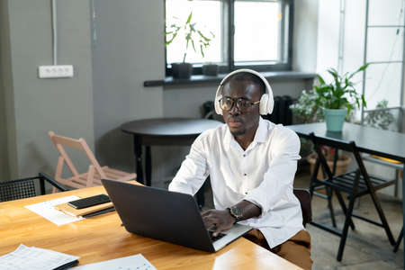 Serious businessman of African ethnicity using laptop by workplace