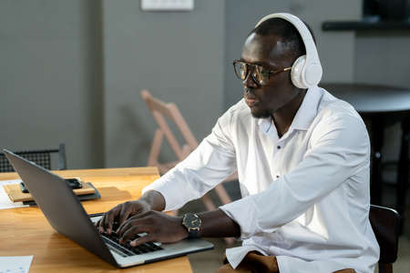 Young businessman of African ethnicity in white shirt and headphones using laptop Фото со стока