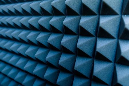 dampen: Dampening acoustical foam on recording studio wall
