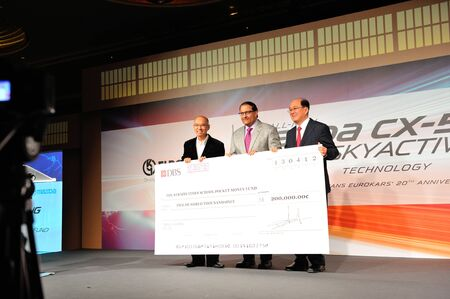 Mr Karsono Kwee, Executive Chairman of Eurokars Group, presenting The Straits Times School Pocket Money Fund cheque to Mr Han Fook Kwang from the Straits Times at the launch of Mazda CX-5 SUV on 13 Apr 2012 Stock Photo - 13161222