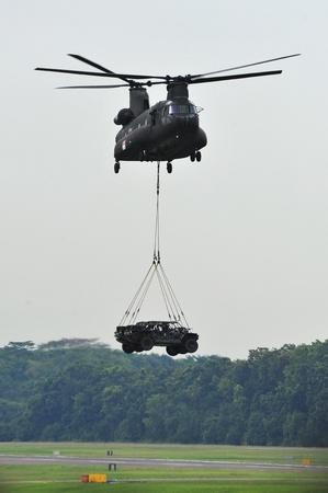 chinook: Repubblica di Singapore Air Force (RSAF) CH-47 Chinook elicotteri militari di atterraggio 2 veicoli leggeri sciopero (LSV) durante RSAF Open House 2011 il 28 maggio 2011 a Singapore Editoriali