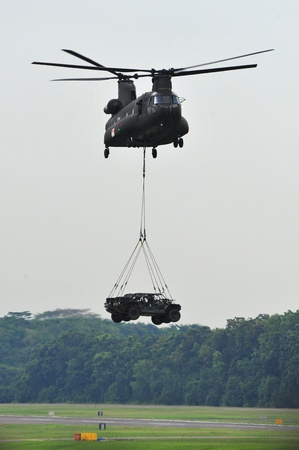 Republic of Singapore Air Force (RSAF) CH-47 Chinook military helicopter landing 2 light strike vehicles (LSV) during RSAF Open House 2011 on May 28, 2011 in Singapore Stock Photo - 13266383