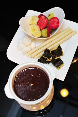 Set of dark chocolate fondue with dipping ingredients photo