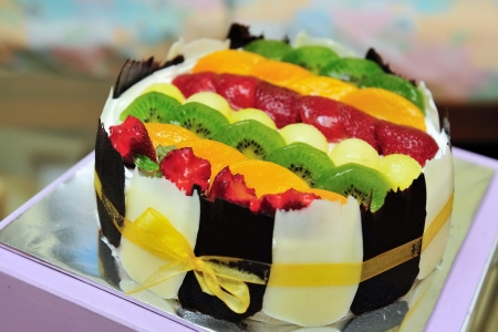 Fruit cake topped with kiwis, strawberries and peaches