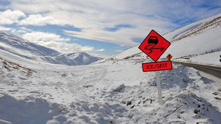 grit: Signs warning drivers of ice and grit on snow mountain roads in New Zealand