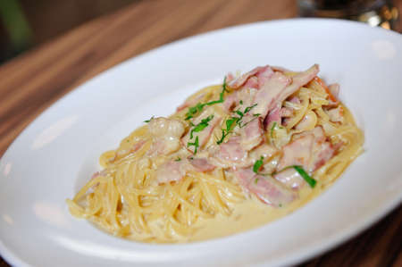 Plate of cream sauce carbonara topped with bacon photo