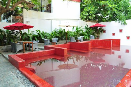 alfresco: Red color swimming pool and alfresco dining area in a resort Editorial