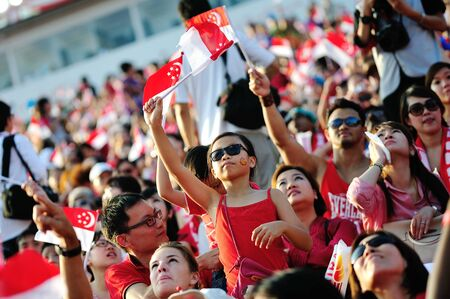 Audience winkt Singapore Fahnen während National Day Parade 2012 am 09. August 2012 in Singapur
