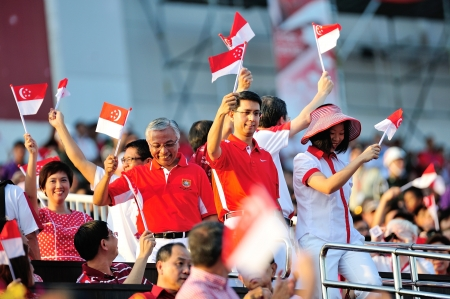Ministers of State entering the gallery and waving flags during National Day Parade 2012 on August 09, 2012 in Singapore