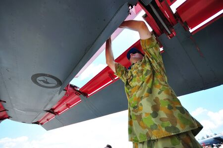 royal air force: Mechanic checking the wing of General Dynamics F-111 fighter jet at Singapore Airshow February 03, 2010 in Singapore Editorial