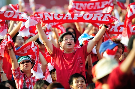 Spectators waving Singapore scarves during National Day Parade 2012 on August 09, 2012 in Singapore